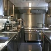 Vue générale de la cuisine : zone laverie à gauche, cuisson au fond et préparation à droite